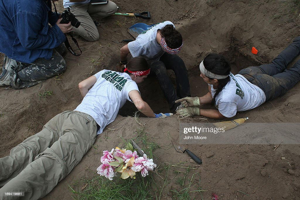 A forensic anthropology team unearths the remains of suspected undocumented immigrants from a gravesite on May 24, 2013 near Falfurrias, Brooks County, Texas. In Brooks County alone, at least 129 immigrants perished in 2012, most from dehydration while making the long crossing from Mexico. Teams from Baylor University and the University of Indianapolis are exhuming the bodies of more than 50 immigrants who died furing their journey. The bodies will be examined and cross checked with DNA sent from Mexico and Central American countries, with the goal of reuniting the remains with families.