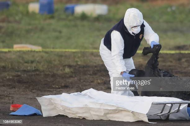 A forensic doctor works with burned bodies after an explosion in a pipeline belonging to Mexican oil company PEMEX on January 19 2019 in Tlahuelilpan...