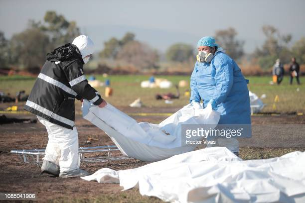 Forensic doctors work with burned bodies after an explosion in a pipeline belonging to Mexican oil company PEMEX on January 19 2019 in Tlahuelilpan...