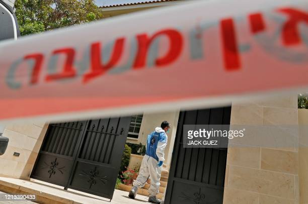 Forensic expert enters the residence of Israel's Chinese ambassador on the outskirts of Tel Aviv, after he was found dead on May 17, 2020. - The...