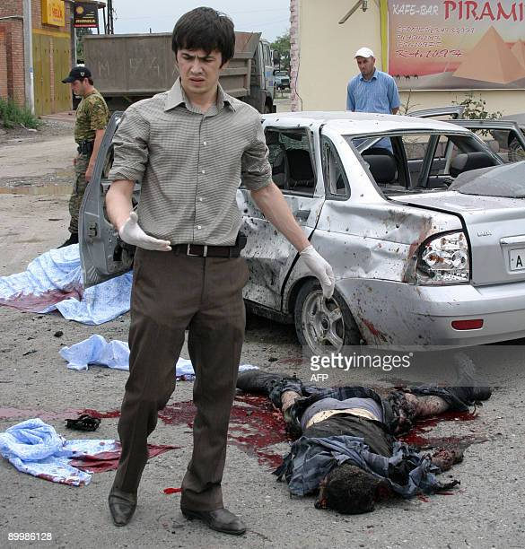 A forensic expert stands near a dead body and a destroyed automobile at the site of a suicide bomber attack in Grozny the capital of the Chechnya...