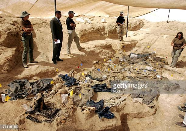 Forensic experts and an Iraqi judge stand near a mass grave containing human skeletons and clothes of people allegedly executed during the regime of...