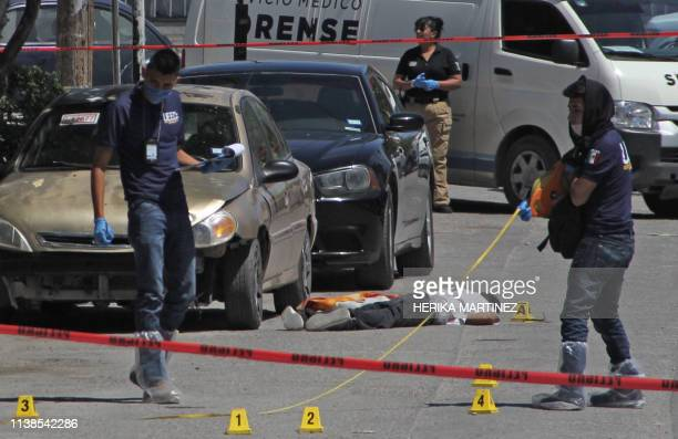 Forensic experts and investigators of the prosecution office work at the crime scene next to a man's corpse in Ciudad Juarez Mexico on April 20 2019...