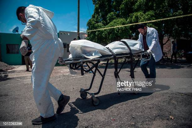 Forensic experts carry the body of a man shot dead in Culiacan Sinaloa on August 1 2018 Mexican Presidentelect Andres Manuel Lopez Obrador who will...