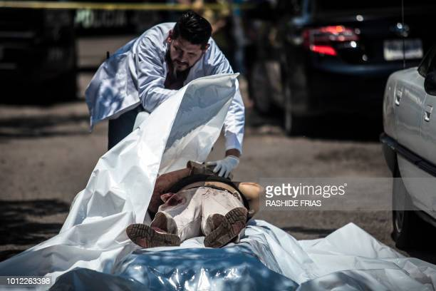 Forensic experts check the body of a man shot dead in Culiacan Sinaloa on August 1 2018 Mexican Presidentelect Andres Manuel Lopez Obrador who will...