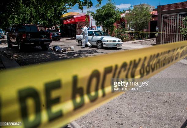 Forensic experts check the body of a woman shot dead in Culiacan Sinaloa on August 1 2018 Mexican Presidentelect Andres Manuel Lopez Obrador who will...