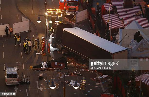 Forensic experts examine the scene around a truck that crashed into a Christmas market on December 20 2016 in Berlin German police said they were...