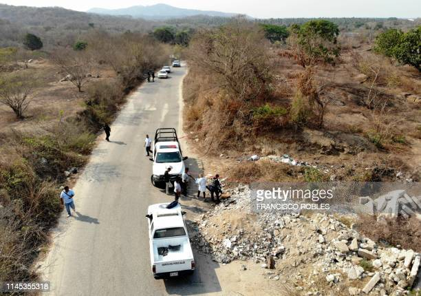 Forensic experts investigators of the prosecution office and policemen work at the crime scene next to a man's corpse in Acapulco Guerrero State...
