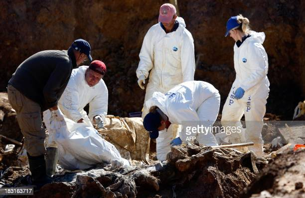Forensic experts members of the International Commission on Missing Persons and Bosnian workers search for human remains at a mass grave in the...