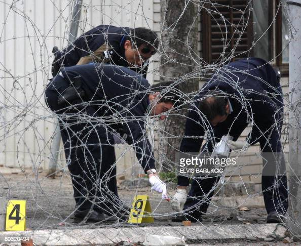 UN forensic experts search the perimeter around the