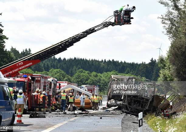 Forensic experts take pictures of the scene where a tour bus burst into flames following a collision with a trailer truck on the highway A9 near...