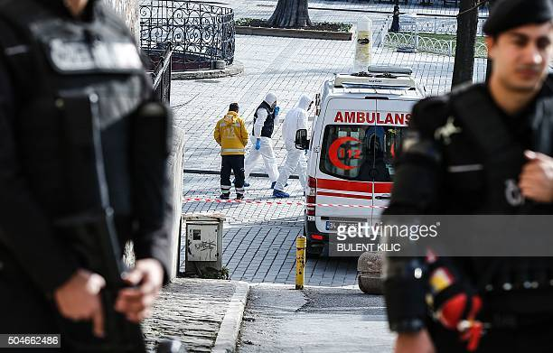 Forensic experts walk near the site of a blast in the Blue Mosque area in Istanbul's tourist hub of Sultanahmet on January 12 2016 At least 10 people...