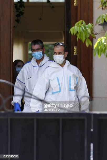 Forensic experts walk out of the residence of Israel's Chinese ambassador on the outskirts of Tel Aviv, after he was found dead on May 17, 2020. -...