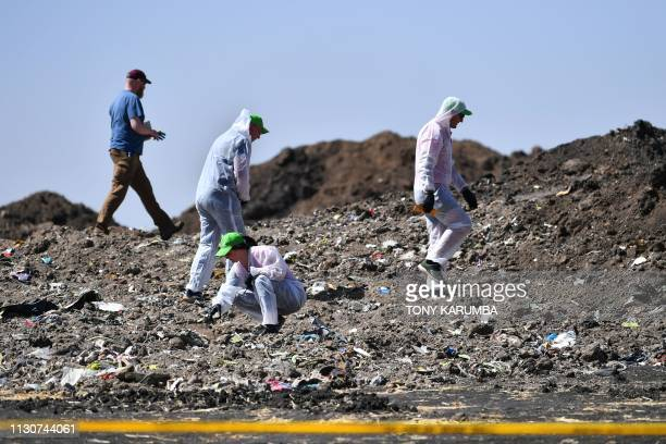 Forensic experts work at the crash site of the Ethiopian Airlines operated Boeing 737 MAX aircraft in which their relatives perished among the 157...