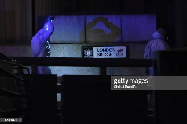 A forensic investigator takes photographs by London Bridge after a number of people are believed to have been injured after a stabbing police have...