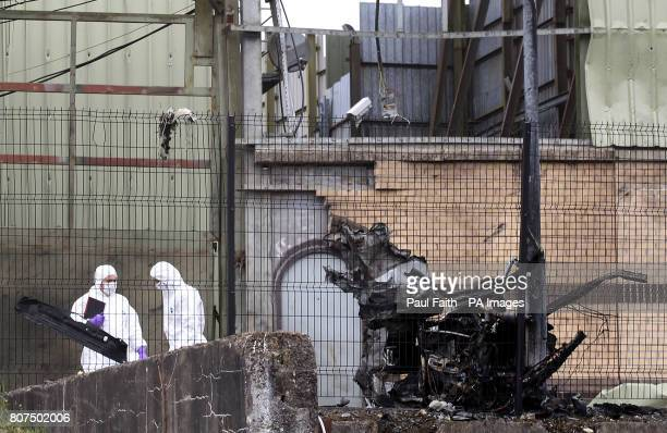 Forensic investigators at the scene of the car bomb attack in Newtownhamilton County Armagh Two people have been injured in a car bomb explosion...