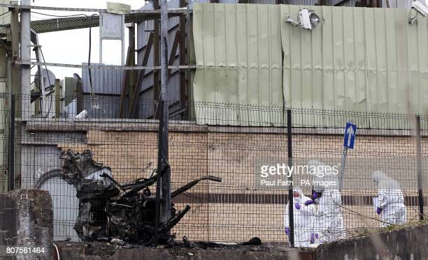 Forensic investigators at the scene of the car bomb attack in Newtownhamilton County ArmaghTwo people have been injured in a car bomb explosion...