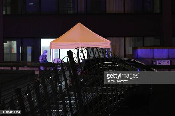 Forensic investigators examine the crime scene on London Bridge after a number of people are believed to have been injured after a stabbing police...