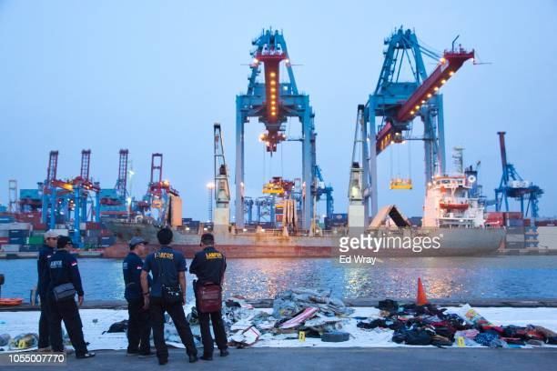 forensic investigators look over some of the wreckage of Lion Air flight JT 610 at the Tanjung Priok port on October 29 2018 in Jakarta Indonesia...