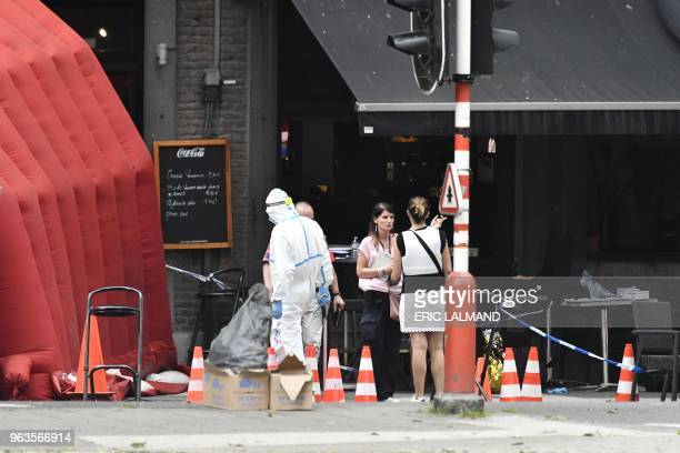 Forensic investogators work at the scene where a gunman shot dead two police officers and a bystander on the Boulevard d'Avroy in the eastern Belgian...