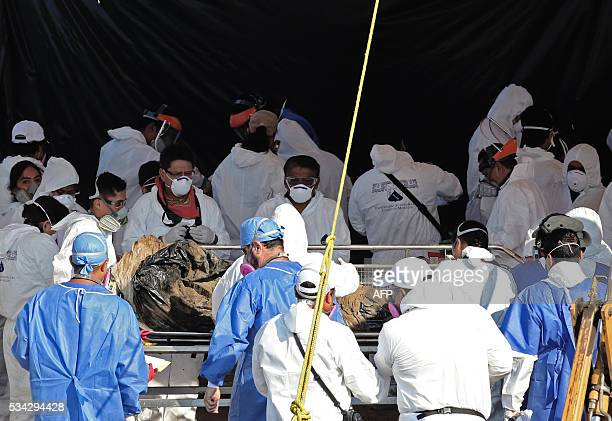 Forensic medical personnel recover a corpse from a mass grave on the third day of work at the cemetry of Tetelcingo, Morelos, Mexico on May 25, 2016....