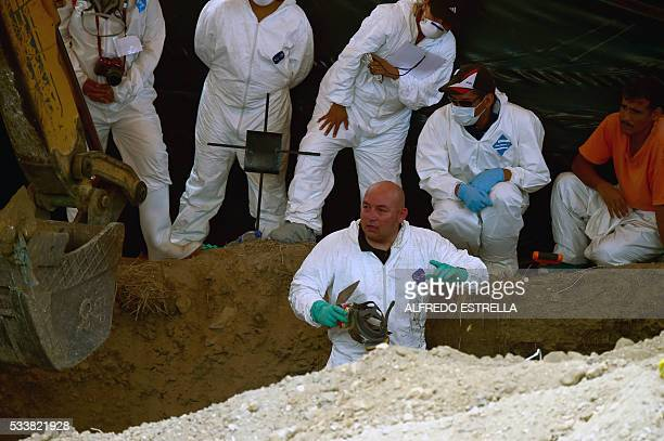 Forensic medical personnel work in the exhumation of 116 bodies found in a mass grave at Tetelcingo community in Morelos State Mexico on May 23 2016...
