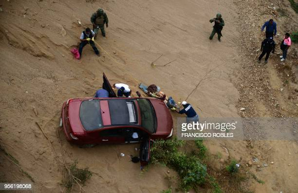 Forensic medical service experts state police and army soldiers work in the rescue of a man's body which was thrown into a ravine inside a vehicle in...