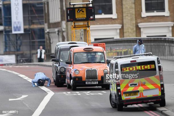 A forensic officer checks under a taxi as they work on London Bridge following last night's terrorist attack on June 4 2017 in London England Police...