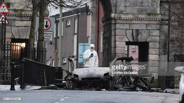 A forensic officer inspects the remains of the van used as a car bomb on an attack outside Derry Court House on January 20 2019 in Londonderry...