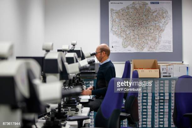 A forensic officer matches firing details and references cartridge cases with a ballistic microscope at the London Metropolitan Police firearm...
