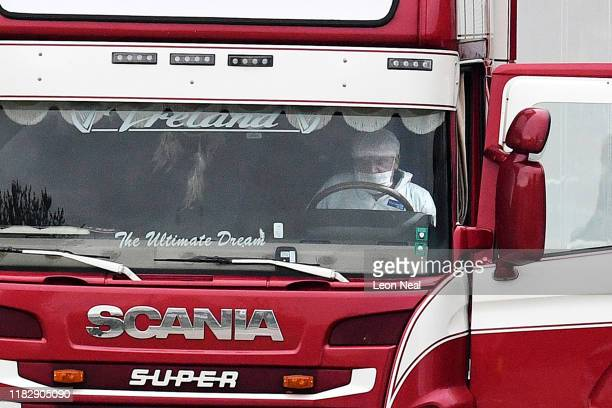 Forensic officer sits at the wheel of a lorry in which 39 bodies were discovered in the trailer, as they prepare move the vehicle from the site on...