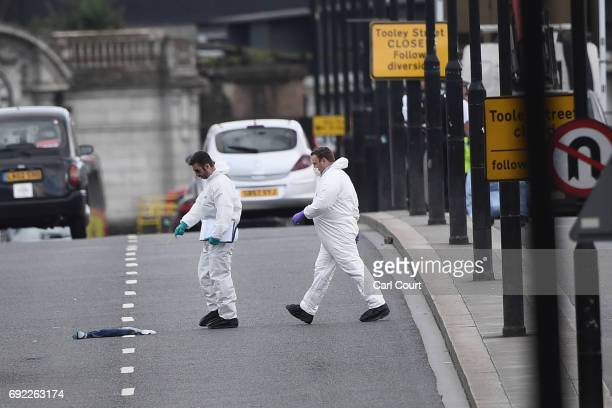 Forensic officers check an item on the ground as they work on London Bridge following last night's terrorist attack on June 4 2017 in London England...