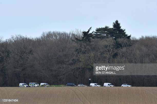 Forensic officers conduct a search in woodland near Ashford, southeast England following the discovery of human remains on March 11, 2021. - An...