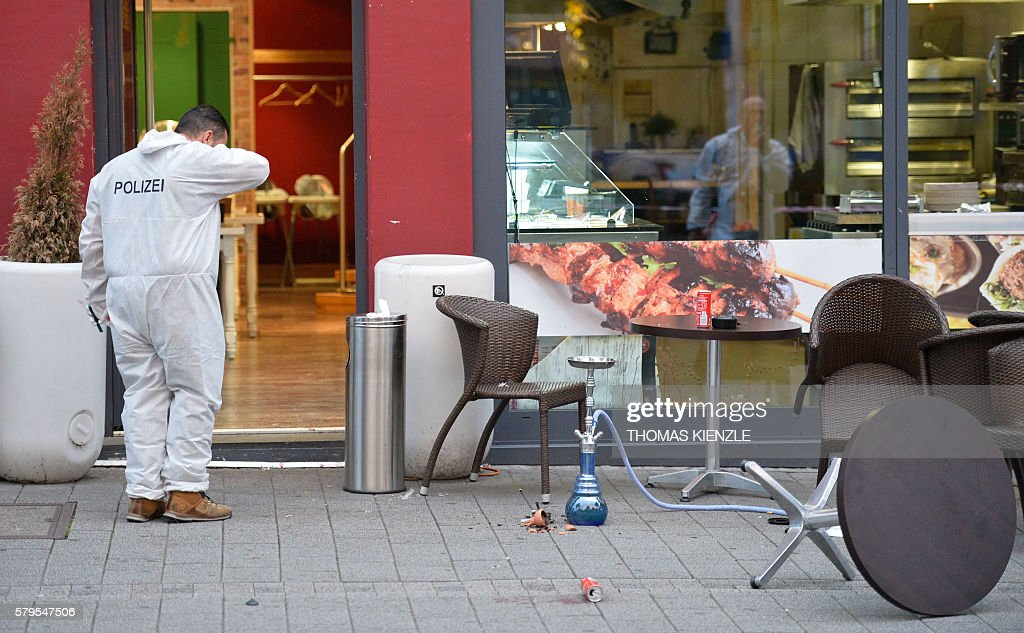 Forensic officers investigate the area in front of the fastfood restaurant in Reutlingen, southwestern Germany, on July 24, 2016 where a Syrian asylum-seeker killed a woman and injured two people with a machete. The man, who was arrested, 'had a dispute' with the woman and killed her 'with a machete' before injuring a second woman and a man, police stated. / AFP / THOMAS