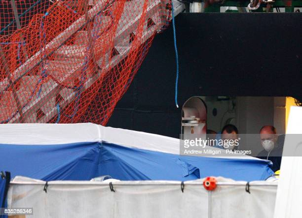 Forensic Officers remove the bodies of the men who were killed when a helicopter crashed in the North Sea from the Caledonian Victory vessel at...