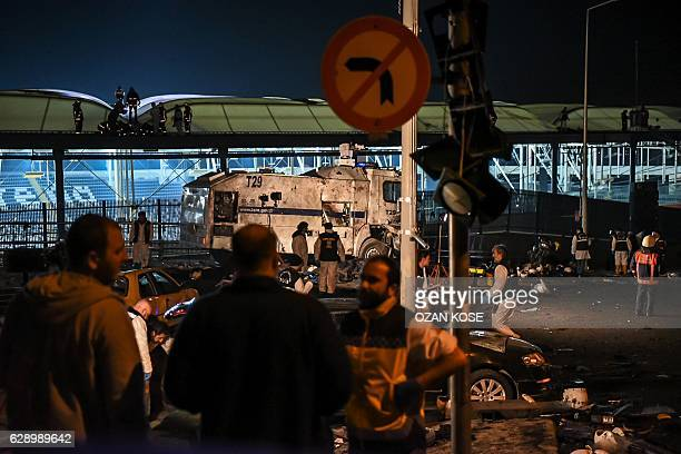 Forensic officers work as emergency officers walk with bodybags on the roof of the Vodafone Arena stadium at the site where a car bomb exploded near...