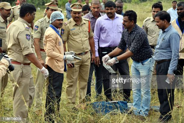 Forensic official ( holds a gun as police officers gather around the body of man at the site where Police officers shot dead four detained gang-rape...