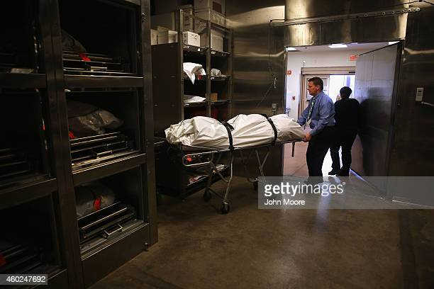 Forensic pathologist Greg Hess handles human remains in the refrigerated morgue of the Pima County Office of the Medical Examiner on December 9 2014...