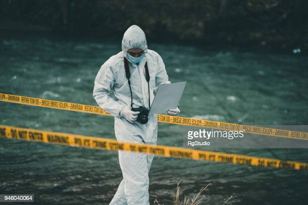 Forensic pathologist holding a ca,era looking down searching for evidence