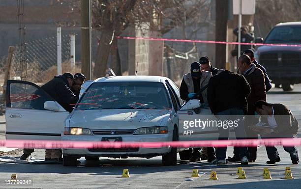 Forensic personnel and investigators check a car where the corpses of two local policemen were found in Ciudad Juarez Chihuahua state on January 27...