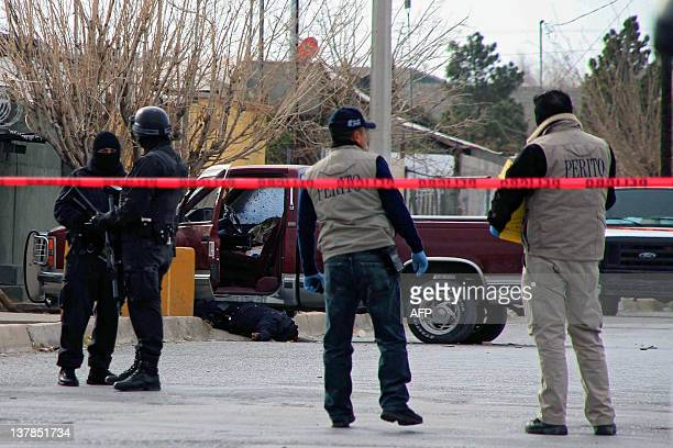 Forensic personnel and investigators watch a truck with the corpse of a policeman in Ciudad Juarez Chihuahua state Mexico on January 28 2012 Tree...