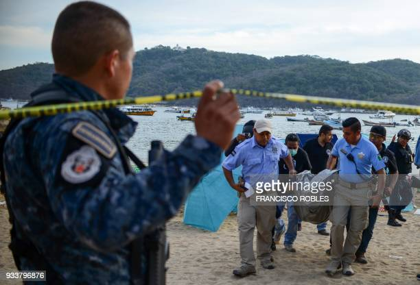 Forensic personnel and police officers carry the body of a murdered man at Caletilla beach in the touristic city of Acapulco Guerrero State Mexico on...