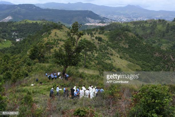 "Forensic personnel and police officers work at the site where an illegal common grave, used by ""Barrio 18"" gang to bury victims kidnapped in a cab,..."