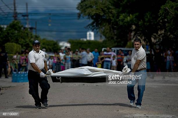 Forensic personnel carry the body of an alleged gang member killed by the police after a shooting at El Pedregal neighborhood in Tegucigalpa on...