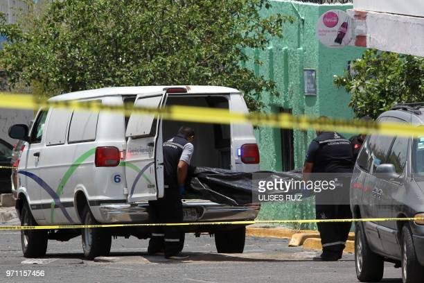 Forensic personnel carry the corpse of one of three people killed during an operation by the Jalisco State police in Guadalajara Mexico on June 10...