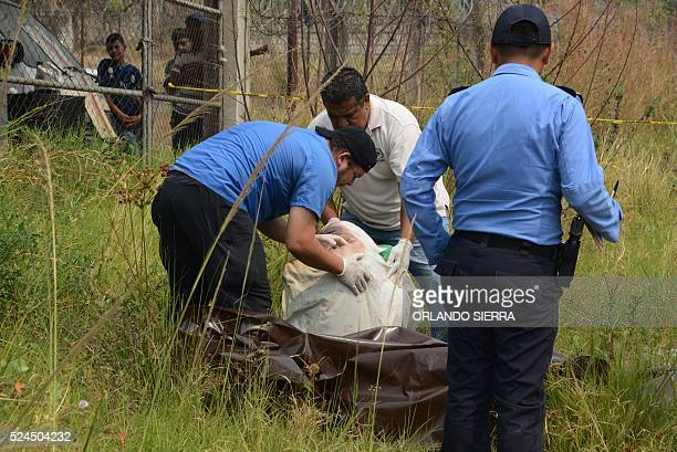 Forensic personnel retrieve the corpse of a young student who was kidnapped and eventually murdered by 'mara' gangsters in Tegucigalpa, on April 26,...