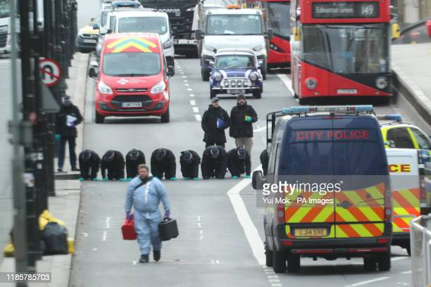 Forensic personnel searching for fingerprints at the cordoned off area on London Bridge in central London after a terrorist wearing a fake suicide...
