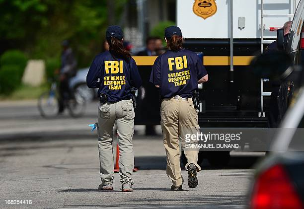FBI forensic personnel walk in front of the house where three women were held captive for a decade on May 7 2013 in Cleveland ohio Three brothers...