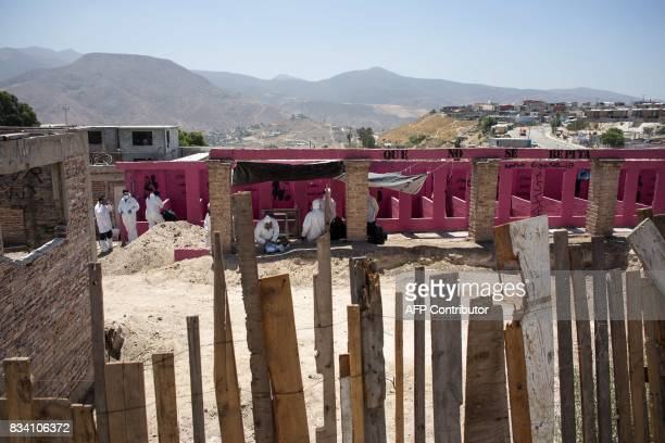 Forensic personnel work at the property where a mass grave has been found in eastern Tijuana Mexico on August 17 2017 More than 600 human bone...