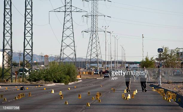 Forensic personnel work on a street in Ciudad Juarez Chihuahua State Mexico on September 7 where three alleged police officers were murdered by...